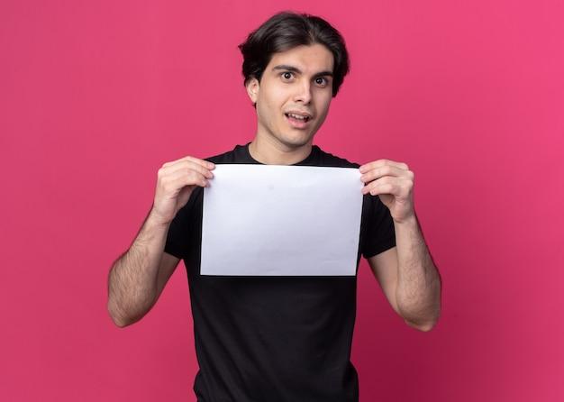 Verwarde jonge knappe kerel die zwart t-shirt draagt ?? die document houdt dat op roze muur wordt geïsoleerd