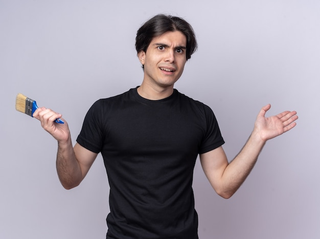 Verwarde jonge knappe kerel die zwarte t-shirt draagt die de verfborstel verspreidende hand houdt die op witte muur wordt geïsoleerd