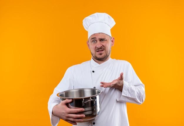 Verwarde jonge knappe kok in uniform van de chef-kok die de ketel vasthoudt en lege hand toont op geïsoleerde oranje muur