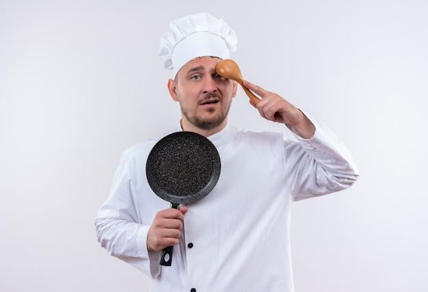 Verwarde jonge knappe kok in uniform van de chef-kok die een koekenpan vasthoudt en een lepel op het voorhoofd zet, geïsoleerd op een witte muur