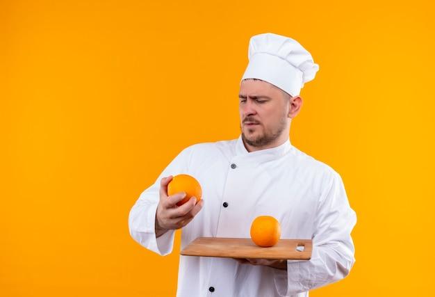 Verwarde jonge knappe kok in uniform van de chef-kok die snijplank en sinaasappel vasthoudt en ernaar kijkt geïsoleerd op oranje muur
