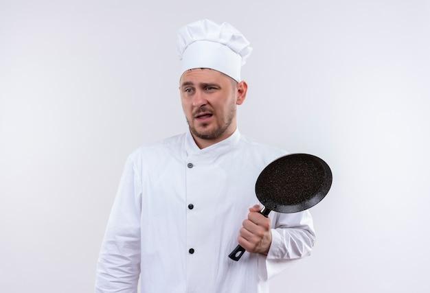 Verwarde jonge knappe kok in uniform van de chef-kok met koekenpan kijkend naar kant geïsoleerd op een witte muur