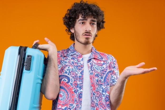 Verwarde jonge knappe krullende reiziger man met koffer en lege hand tonen op geïsoleerde oranje ruimte