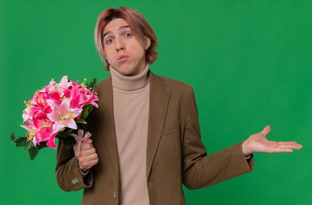 Verwarde jonge knappe man die een boeket bloemen vasthoudt en zijn hand openhoudt Gratis Foto