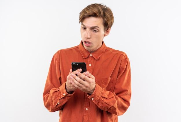 Verwarde jonge knappe man met een rood shirt die de telefoon vasthoudt en bekijkt