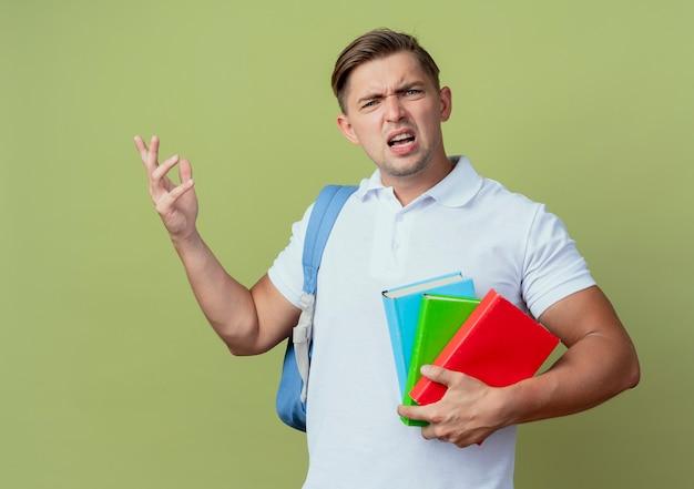 Verwarde jonge knappe mannelijke student die de boeken van de achterzakholding draagt die op olijfgroene achtergrond worden geïsoleerd
