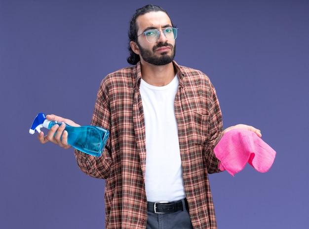 Verwarde jonge knappe schoonmaakster die een t-shirt draagt met een spuitfles met een vod die handen verspreidt, geïsoleerd op een blauwe muur