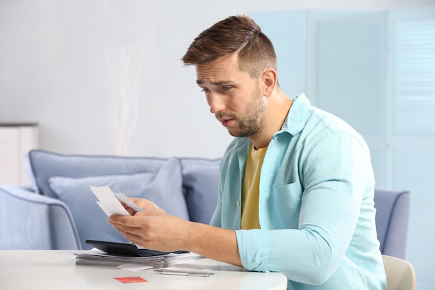 Verwarde jonge man die belastingen thuis berekent