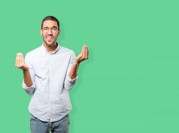 Verwarde jonge man die een italiaans gebaar maakt van niet begrijpt