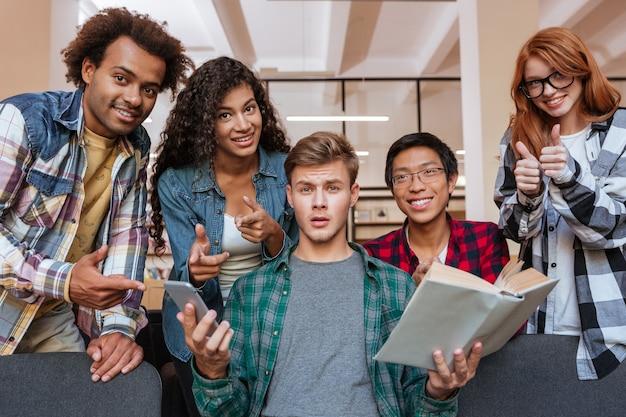 Verwarde jonge man met boek en mobiele telefoon met zijn gelukkige vrienden