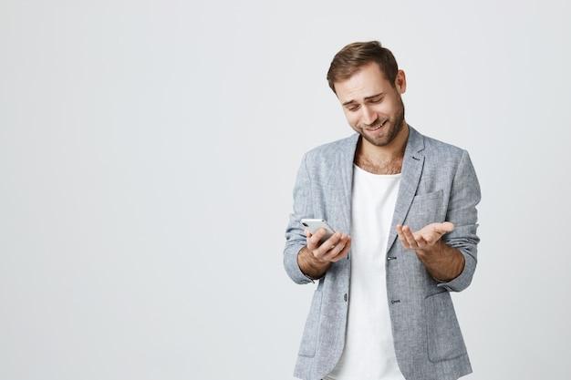 Verwarde jonge man schouderophalend op mobiele telefoon scherm, glimlachend