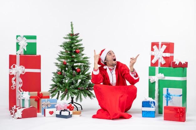 Verwarde jonge man verkleed als kerstman met geschenken en versierde kerstboom zittend op de grond op zoek naar boven op witte achtergrond