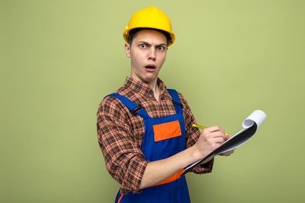 Verwarde jonge mannelijke bouwer schrijft op klembord in uniform