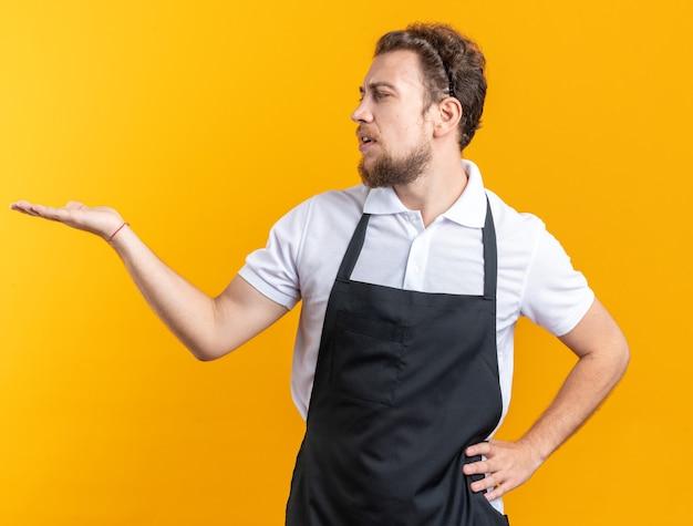 Verwarde jonge mannelijke kapper die een uniform draagt en doet alsof hij iets vasthoudt en kijkt naar iets dat de hand op de heup legt, geïsoleerd op een gele muur