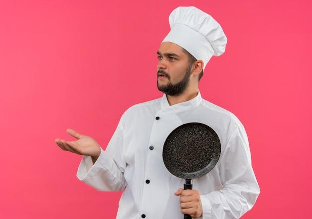 Verwarde jonge mannelijke kok in uniform van de chef-kok die een koekenpan vasthoudt en een lege hand laat zien die naar de zijkant kijkt die op een roze muur is geïsoleerd