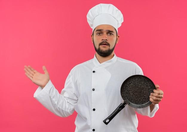 Verwarde jonge mannelijke kok in uniform van de chef-kok die een koekenpan vasthoudt en een lege hand toont die op een roze muur is geïsoleerd