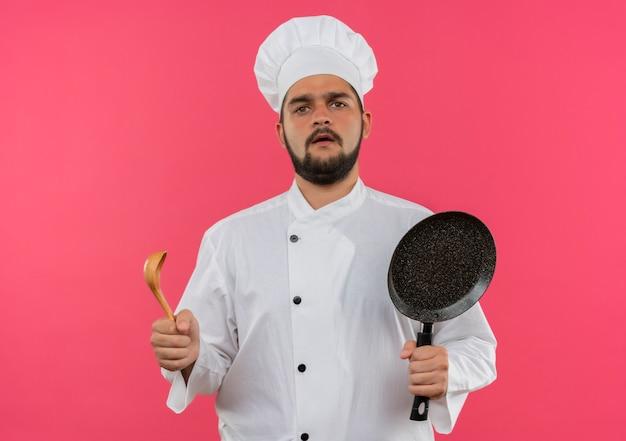 Verwarde jonge mannelijke kok in uniform van de chef-kok met koekenpan en lepel geïsoleerd op roze muur