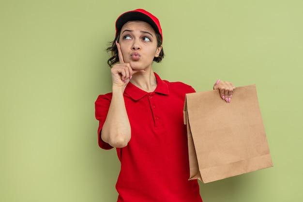 Verwarde jonge mooie bezorger die papieren voedselverpakking vasthoudt en omhoog kijkt