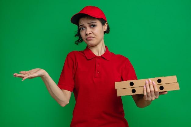 Verwarde jonge mooie bezorger die pizzadozen vasthoudt en hand open houdt