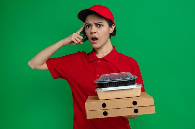 Verwarde jonge mooie bezorger die voedselcontainers en verpakkingen op pizzadozen vasthoudt
