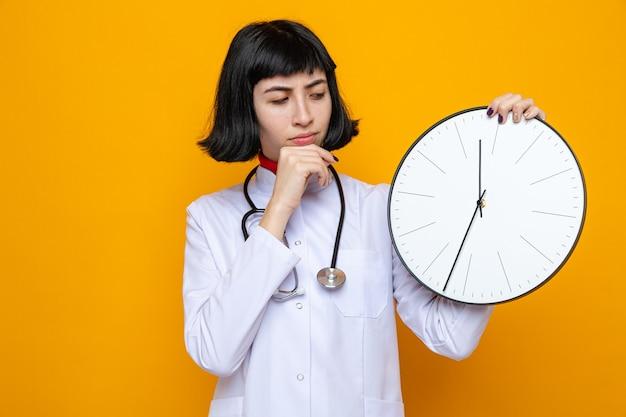 Verwarde jonge, mooie blanke vrouw in doktersuniform met een stethoscoop die de klok vasthoudt en haar hand op haar kin legt