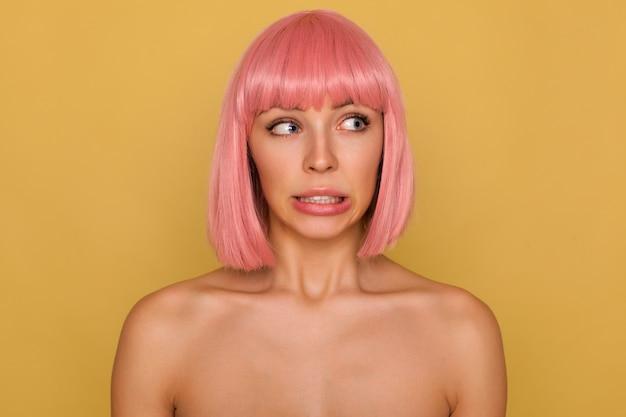Verwarde jonge mooie blauwogige rozeharige vrouw met bob-kapsel dat haar tanden laat zien terwijl ze beschaamd haar mond draait, geïsoleerd over mosterdmuur