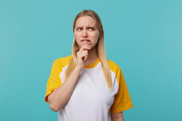 Verwarde jonge mooie blonde vrouw met casual kapsel bedachtzaam fronsen haar gezicht en houden kin met opgeheven hand, geïsoleerd op blauwe achtergrond