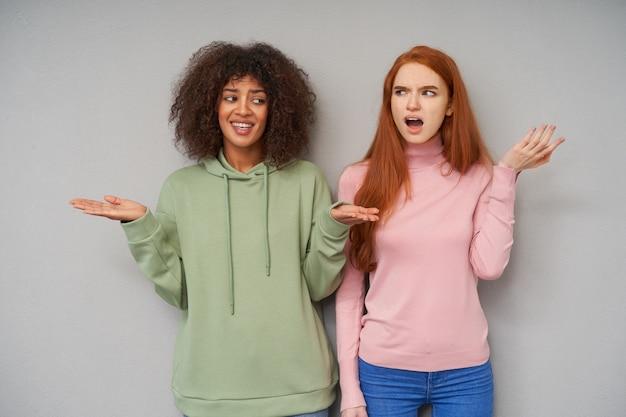 Verwarde jonge mooie dames die verward hun handpalmen en fronsende wenkbrauwen optillen terwijl ze in vrijetijdskleding over een grijze muur staan
