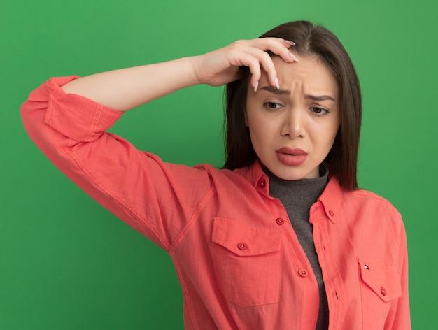 Verwarde jonge mooie vrouw die hand op het hoofd zet en naar beneden kijkt geïsoleerd op groene muur