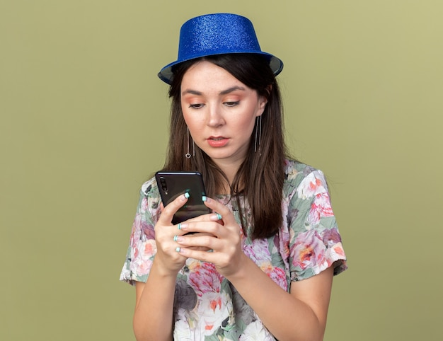 Verwarde jonge mooie vrouw met een feesthoed die vasthoudt en naar een telefoon kijkt die op een olijfgroene muur is geïsoleerd