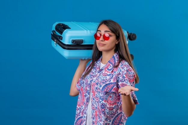Verwarde jonge mooie vrouwentoerist die rode zonnebril draagt die reiskoffer houdt twijfelachtig schouderophalend die zich over geïsoleerde blauwe ruimte bevindt