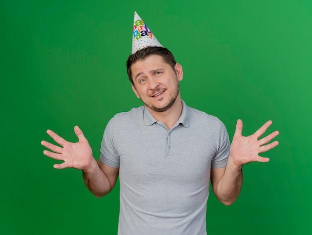 Verwarde jonge partij kerel die verjaardag glb verspreidende handen draagt die op groen worden geïsoleerd