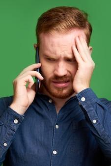 Verwarde jonge roodharige ier met baard die voorhoofd fronst en gezicht bedekt tijdens een telefoongesprek