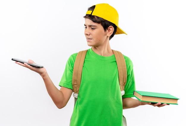 Verwarde jonge schooljongen die een rugzak draagt met een dop die een boek vasthoudt en naar de telefoon kijkt in zijn hand geïsoleerd op een witte muur