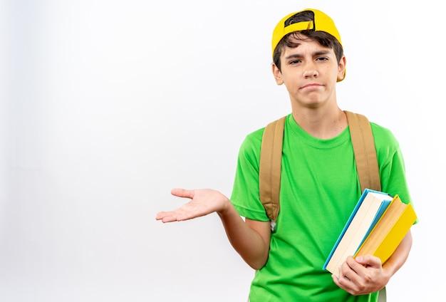 Verwarde jonge schooljongen die een rugzak draagt met een pet die boeken vasthoudt die de hand spreiden?