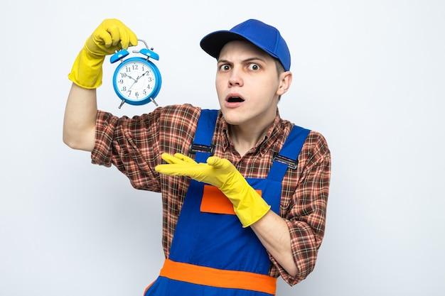 Verwarde jonge schoonmaakster met uniform en pet met handschoenen vast en wijst met de hand op de wekker