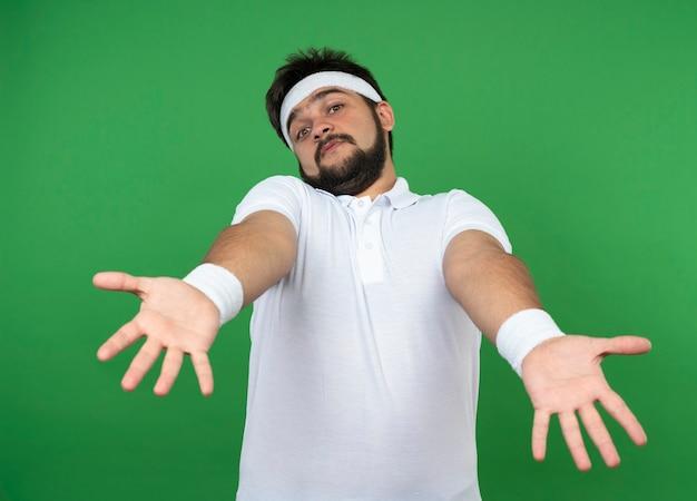 Verwarde jonge sportieve man met hoofdband en polsband die handen uithouden die op groene muur worden geïsoleerd