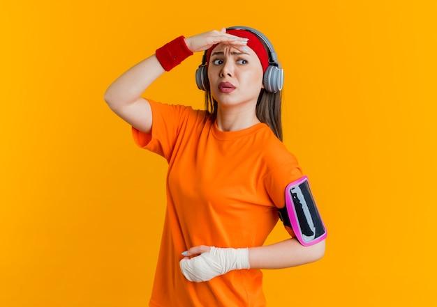 Verwarde jonge sportieve vrouw die hoofdband en polsbandjes en hoofdtelefoons draagt