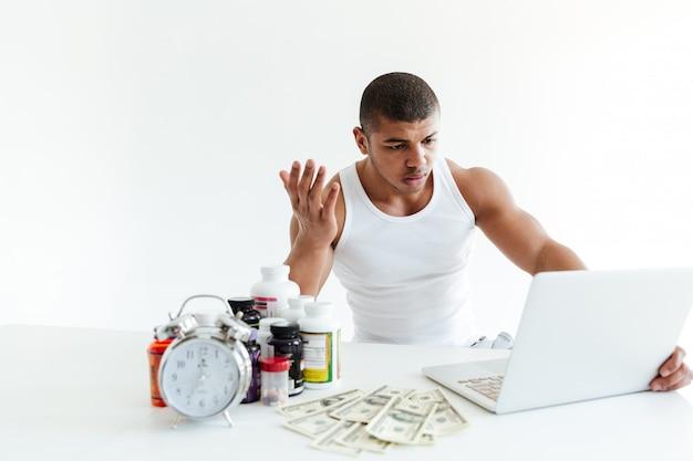 Verwarde jonge sportman dichtbij geld en sportvoeding die laptop met behulp van
