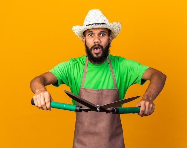 Verwarde jonge tuinman afro-amerikaanse man met een tuinhoed met tondeuses geïsoleerd op een oranje muur