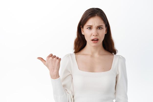 Verwarde jonge vrouw die opzij wijst naar een vreemd spandoek, naar voren staart, vragen stelt, tegen de witte muur in de studio staat