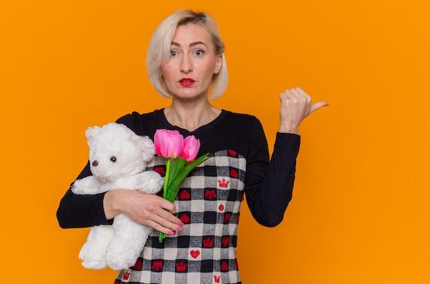 Verwarde jonge vrouw in mooie jurk met boeket tulpen en teddybeer als cadeau wijzend met duim naar achteren en viert internationale vrouwendag staande over oranje muur