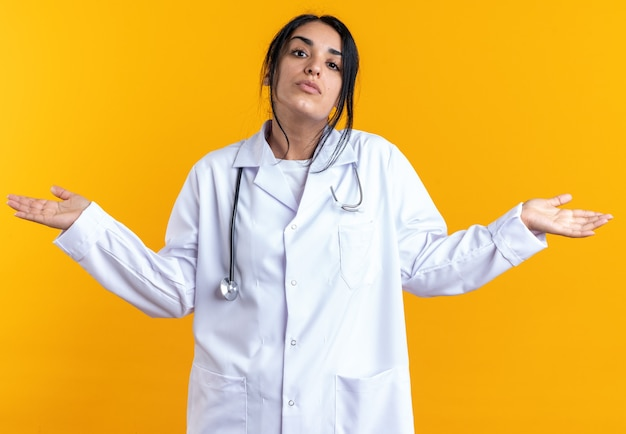 Verwarde jonge vrouwelijke arts die een medisch gewaad draagt met een stethoscoop die handen uitspreidt die op een gele muur zijn geïsoleerd