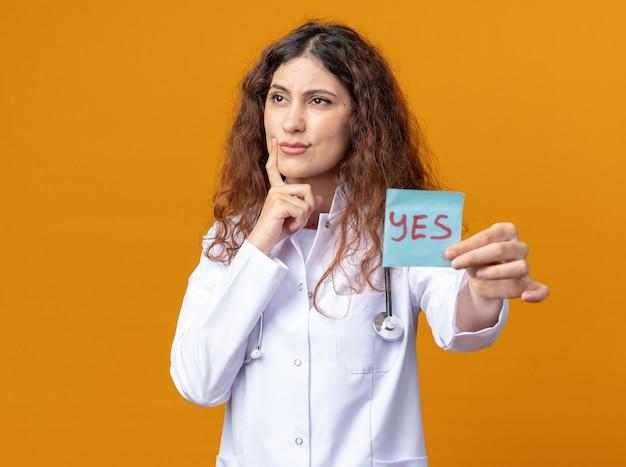 Verwarde jonge vrouwelijke arts die een medisch gewaad en een stethoscoop draagt en naar de zijkant kijkt die zich uitstrekt ja notitie vinger op het gezicht houden geïsoleerd op een oranje muur met kopieerruimte