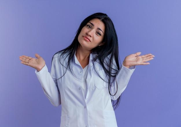 Verwarde jonge vrouwelijke arts die medische mantel draagt die met lege handen kijkt