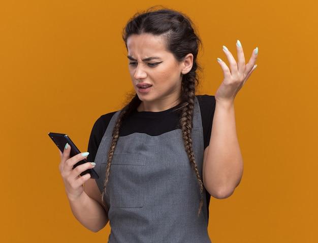 Verwarde jonge vrouwelijke kapper in uniform houden en kijken naar telefoon spreidende hand geïsoleerd op oranje muur