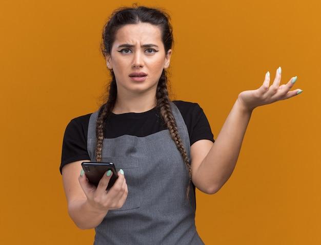 Verwarde jonge vrouwelijke kapper in uniform met telefoon verspreidende hand geïsoleerd op oranje muur orange