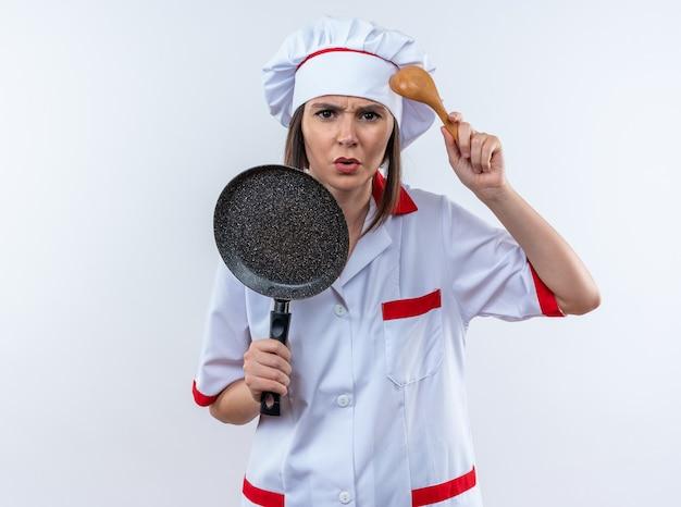 Verwarde jonge vrouwelijke kok die een chef-kok uniform draagt en een koekenpan vasthoudt met een lepel geïsoleerd op een witte muur