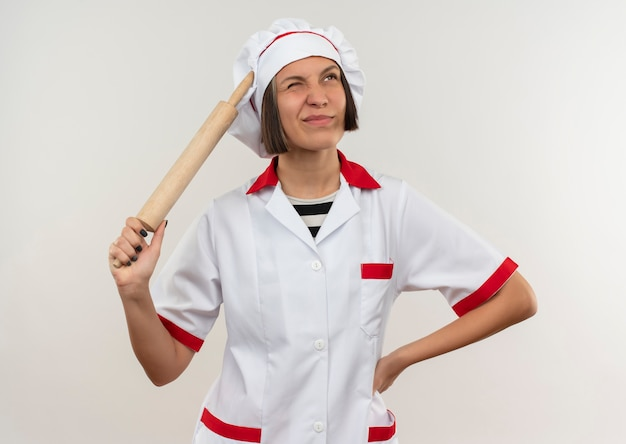 Verwarde jonge vrouwelijke kok in chef-kok uniforme deegroller houden en hand zetten taille opzoeken geïsoleerd op wit