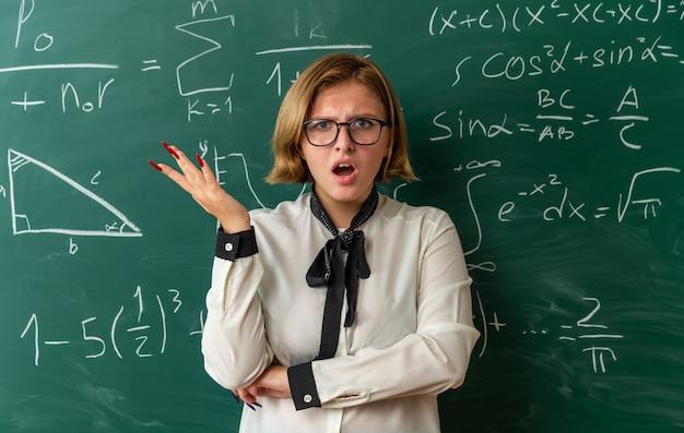Verwarde jonge vrouwelijke leraar met een bril die voor het schoolbord staat en de hand in de klas verspreidt